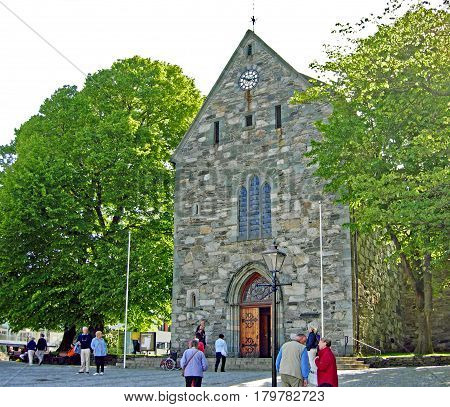 Stavanger, Norway - June 5, 2009: People are waiting in front of Stavanger Cathedral (Stavanger domkirke), the oldest bishop's church in Norway.