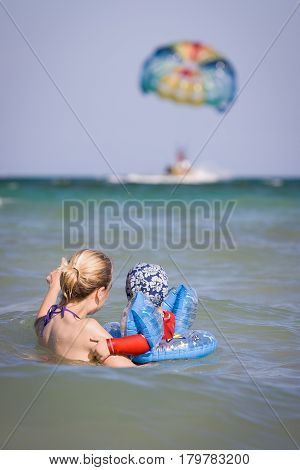 Beautiful young woman with her baby son swimming in the sea on a sunny day. Happy family on vacations. Mother and child swimming and looking at the parachute in the ocean.