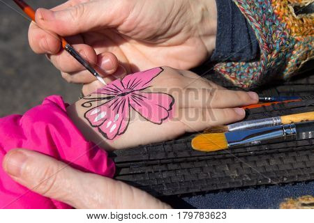 Child's body painting on his hand a pink butterfly painted with a brush