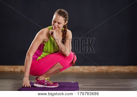 Young slim woman in yoga class making beautiful asana exercises. Healthy lifestyle in fitness club. Woman in the sportwear, pink legginga and green t-shirt. In the yogastudio on the violet yoga mat.