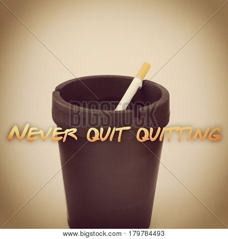 Cigarette in black ashtray isolated on white background with effects and text. Never quit quitting.