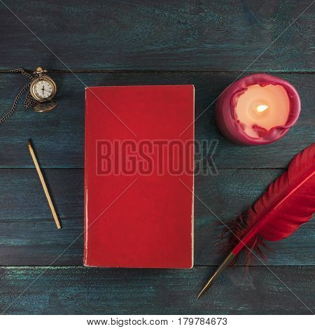 A square mockup with a blank red book cover, a vintage chain watch, a burning candle, a match, and a quill pen