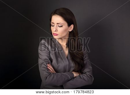 Unhappy Resentful Business Woman In Suit With Folded Arms Looking Down On Dark Grey Background