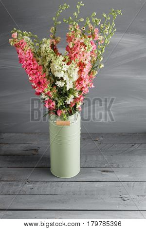 Delphinium of pink color and lemon in vintage vase on gray background.