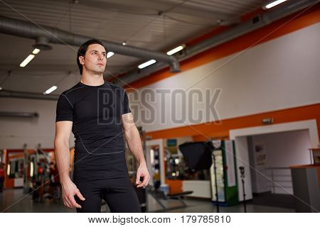 Muscular young athletic built sportsman standing against hall of the gym. Sportsman in the black sportwear, t-shirt and shorts. Horizontal portrait. Confidence and determination. Healthy lifestyle.