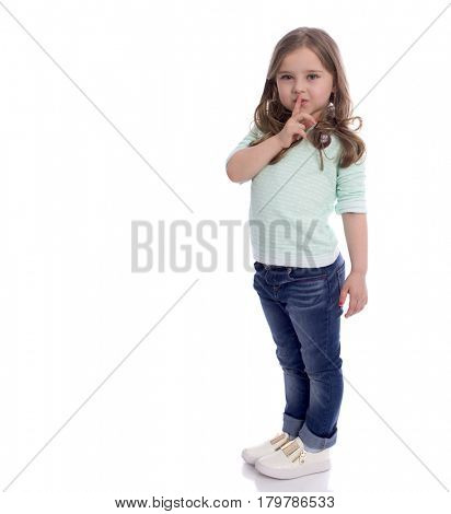 Little girl requires silence. Young beautiful kid has put forefinger to lips as sign of silence, isolated on white background