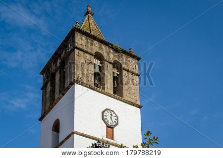 Close view of old tower of Icod de los Vinos with medieval bells and city clock. Icod old town, Tenerife, Spain.