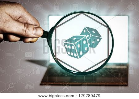 Hand holds the magnifying glass in front of an open notebook. Among the many icons attention is focused on the dice icon. Casino search gambling fortune.