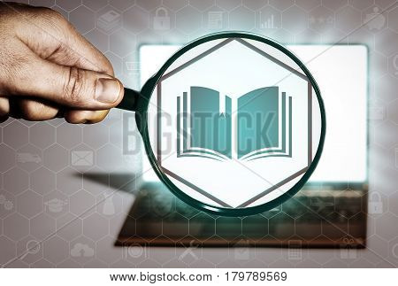Hand holds the magnifying glass in front of an open notebook. Among the many icons attention is focused on the book icon. Educational programs purchase of books library.