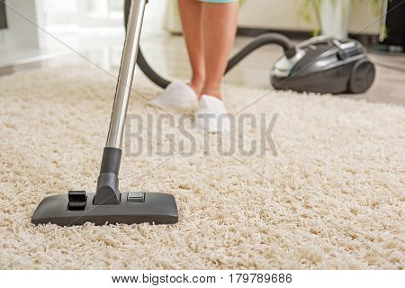 Woman is hoovering carpet with modern vacuum cleaner. Close up of nozzle and female legs