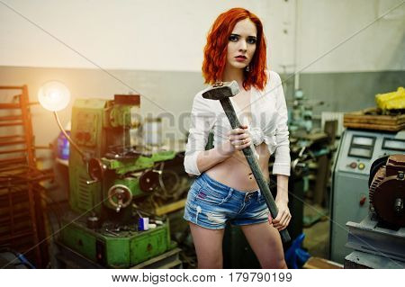 Red Haired Girl Wear On Short Denim Shorts And White Blouse With Hammer At Hands Posed At Industrial