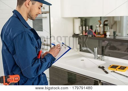Concentrated handyman is keeping map-case and writing on sheet of paper. He standing at cook room