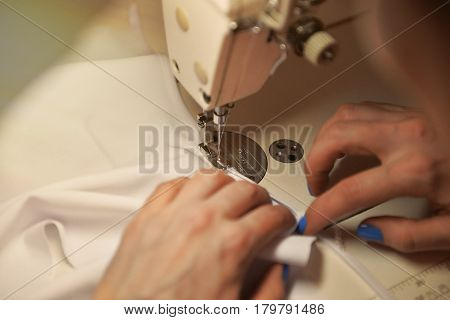 Close-up of working sewing machine. Sewing machine foot on material with threaded needle ready to sew.