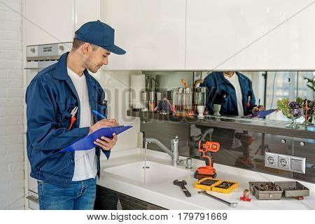 Repairman is holding folder and pen. He standing near countertop, full of tools