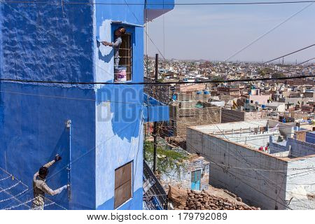 Jodhpur, India - March 8, 2016: Unidentified indian men painting house in blue color into the Blue City Jodhpur, India.