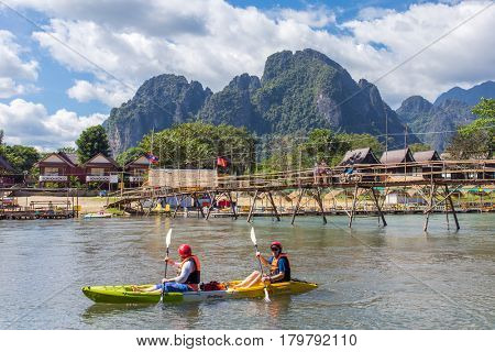 Vang Vieng, Laos - January 19, 2017: Unidentified tourists are rowing kayak boats in Nam Song River in Vang Vieng, Laos