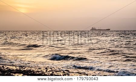 Travel to Middle East country Kingdom of Jordan - yellow sundown over Gulf of Aqaba on Red Sea in winter poster