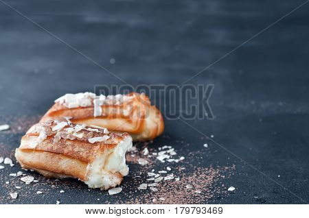eclairs with almond flakes on a dark concrete background