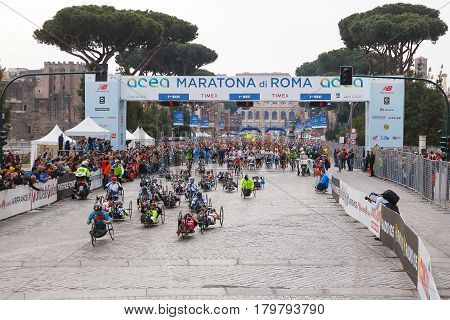 Rome Italy - April 2 2017: hand cycle the departure of the athletes on Via dei Fori Imperiali the Coliseum on background.