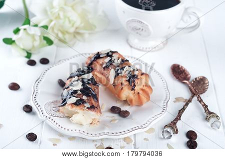 eclairs with cup of coffee and flovers on a white wooden background. Valentines day with breakfast