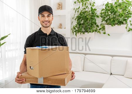 Happy smiling deliveryman is holding boxes and clipboard. He standing in room and looking at camera with interest. Portrait