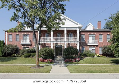 Condominium building in suburbs with front balcony and white pillars.