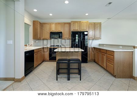 Kitchen in suburban home with oak wood cabinetry and center island with stools.