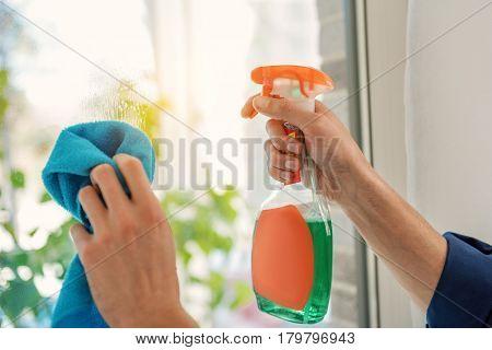 Man is using detergent spray and rag to make glass spotless. Close-up of his hands