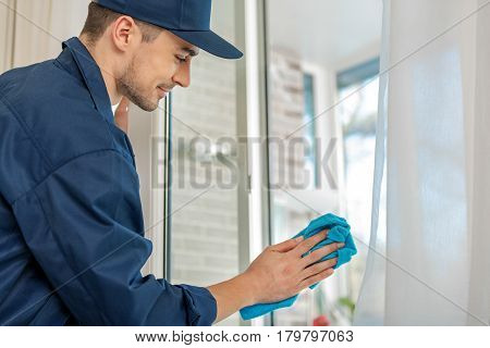Attentive male person is making window clean with blue rag. He standing afore casement