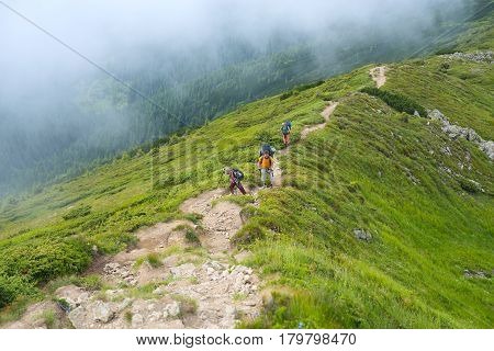 Travelers - men and boy with backpacks rise along the ridge in the haze that the wind brings. Interesting and difficult adventure.