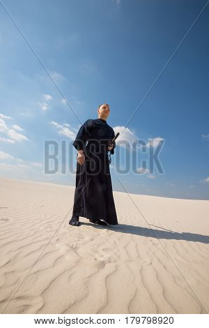 Man Warrior In Traditional Japanese Clothes Stands In Desert