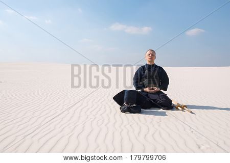 Man In Traditional Armor For Kendo Meditates Before The Practice Of Martial Art