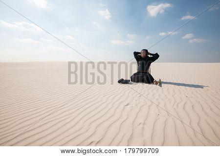 Man Is Sitting In The Middle Of The Desert And Dresses Traditional Armor