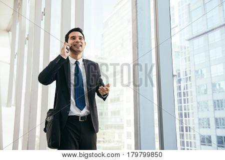 Man on smart phone - young business man in airport. Casual urban professional businessman using smartphone smiling happy inside office building or airport. Handsome man wearing suit indoors.