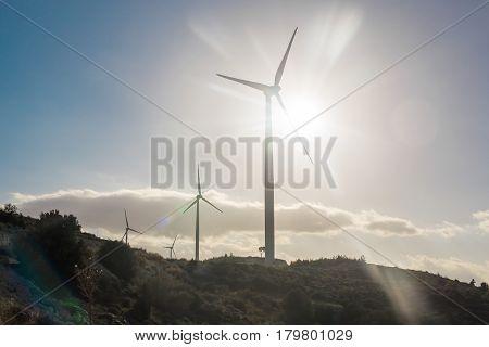 Green renewable energy concept - wind generator turbines in sky.