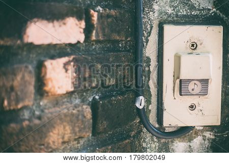 Rustic front gate door bell on brick wall gate