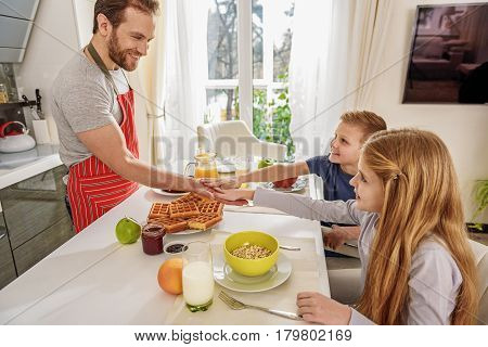 Give me high five. Happy father and children are holding hands together. They are sitting at table in kitchen and smiling