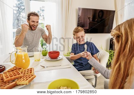 Carefree children are playing with spoons while sitting at table in kitchen. Their father is cheering them up and laughing