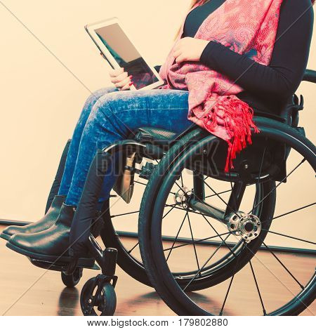 Crippled person with tablet. Young disabled female surfing on web. Internet technology education disability concept.
