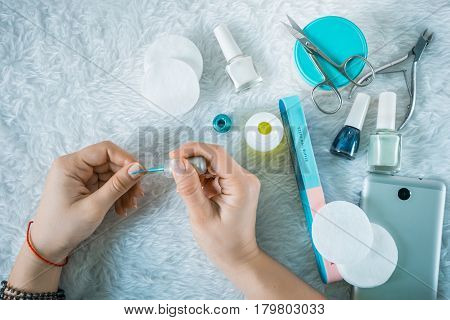 Set for manicure with laptop and smartphone hads paints nails on white fluffy background