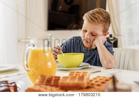 Again cereals. Sad boy is eating breakfast with unwillingness. He is sitting at table in kitchen