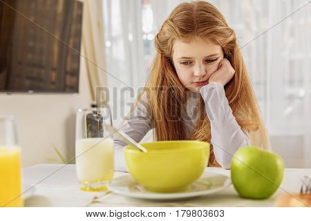 I do not want to eat this. Bored girl is looking at bowl with cereals with disgust. She is sitting at table in kitchen