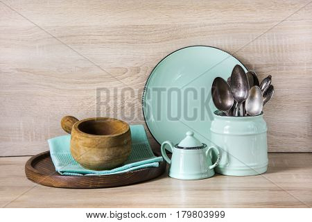 Turquoise crockery tableware dishware utensils and stuff on wooden table-top. Kitchen still life as background for design. Image with copy space.