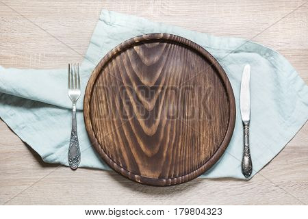 Rustic table set with wooden plate and napkins on wooden table-top. Top view. Image with copy space.