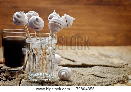 Berries marshmallows with glass of coffee on wood background