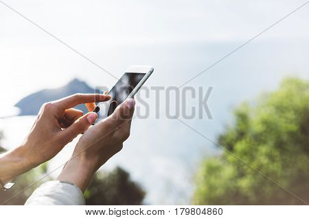 Hipster girl texting message on smartphone mobile close up view tourist hands using gadget phone on device on background perspective mountains and sky landscape; finger touch screen cellphone mockup