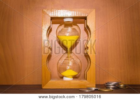 glossy old-style hourglass standing on wooden table with coins