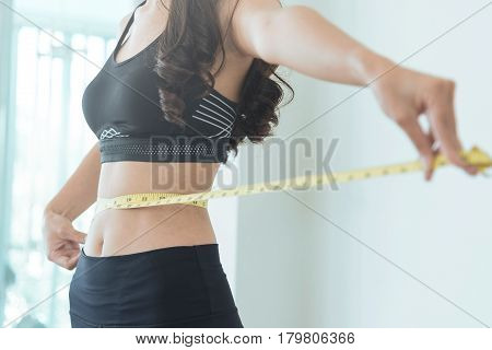 Close up of Slim Asian woman waist with measuring tape. copy space. Woman in black sportswear on white isolated background.