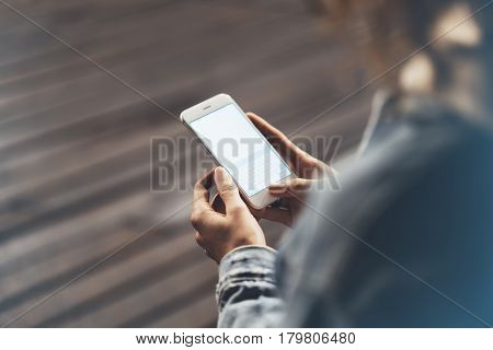 Girl pointing finger on screen smartphone on background wooden floor in night atmospheric city hipster using in female hands and texting mobile phone mockup glitter street lifestyle blured backdrop