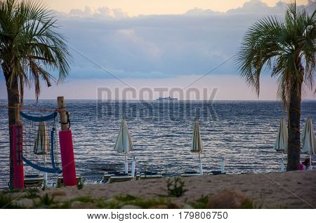 Beautiful sunset landscape with cruising boat on the ocean tropical beach with palms sardegna italy